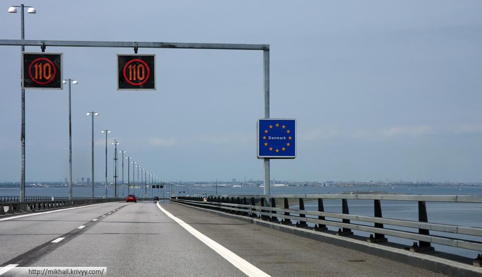 Съезд с моста к тоннелю. Предупредительные знаки, о том что на той стороне Дания. На заднем плане Копенгаген.