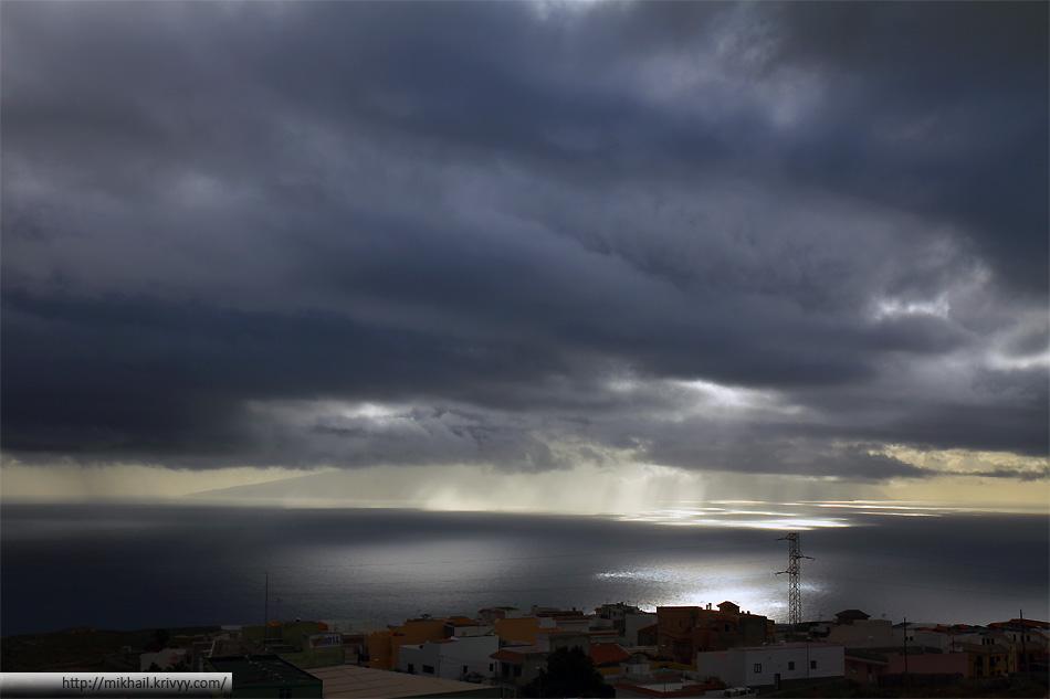 Тучи, дождь и лучи солнца над островм Ла Гомера (Канары). Вид с острова Тенерифе.