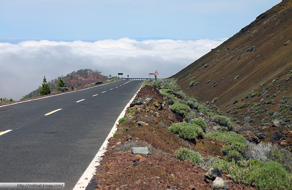 """Шоссе TF-38 проходит прямо у подножия вулкана """"Самара"""" (Samara). Высота 1600 метров. Над океаном облака."""