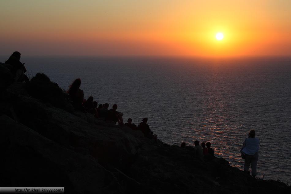 Туристы и закат у маяка Акротири, Санторини.