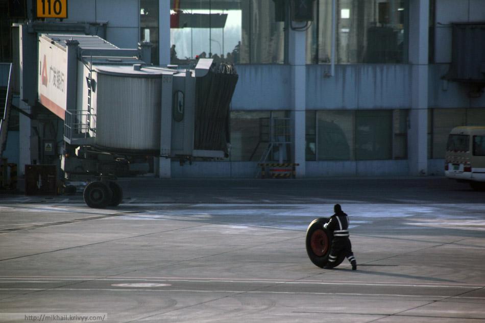 Сотрудник Пекинского аэропорта катит колесо снятое с нашего Airbus A330-300.