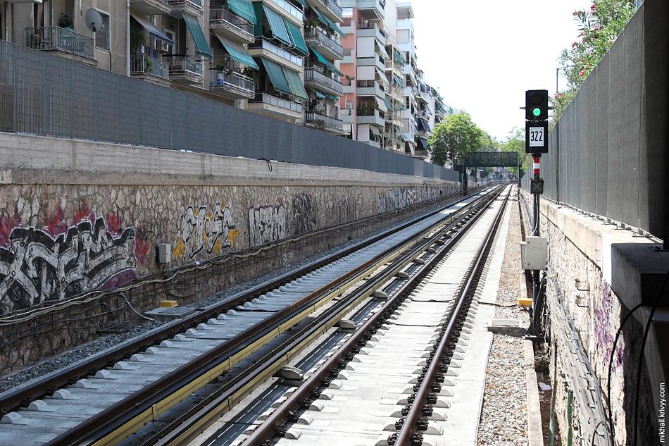 Афинское открытое метро. Оцинкованное ограждение из сварной сетки. Не очень удачное фото. Тут выемка из-за выхода из под земли. Дальше остается только забор из сварной сетки на небольшом бетонном основании.