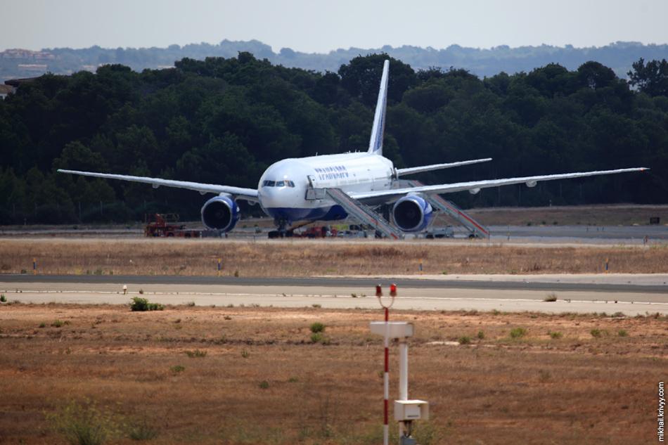 12:19 А вот и Boeing-777 авиакомпании Трансаэро. Грузят багаж. Некоторая размытость связана с атмосферными искажениями. На улице +34 и теплый воздух поднимается от земли.