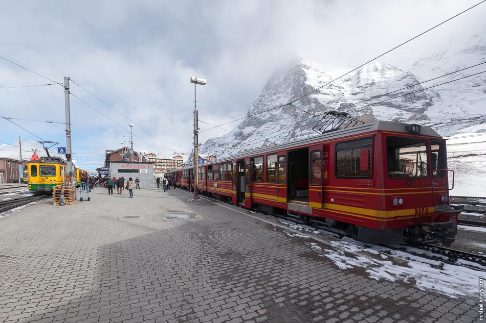 "Станция Клайне-Шайдег (Kleine Scheidegg). Справа поезд железной дороги Юнгфрау (Jungfraubahn) следующий до Юнгфрауйох (Jungfraujoch), слева поезд ""Венгернальп"" (Wengernalpbahn) следующий до Лаутербруннен (Lauterbrunnen)"