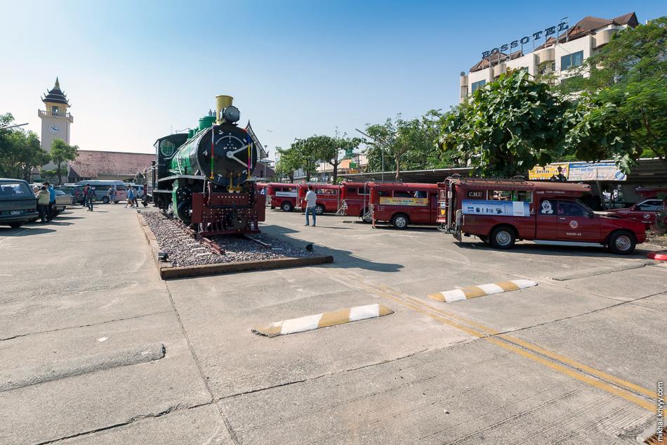 Паровоз на привокзальной площади Чингмая. Красные пикапы - это местный общественный транспорт (Сонгхэв).