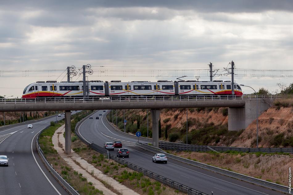 Электропоезд Serie 81 de SFM пересекает автомагистраль Ma-13 в районе города Инка (Inca).