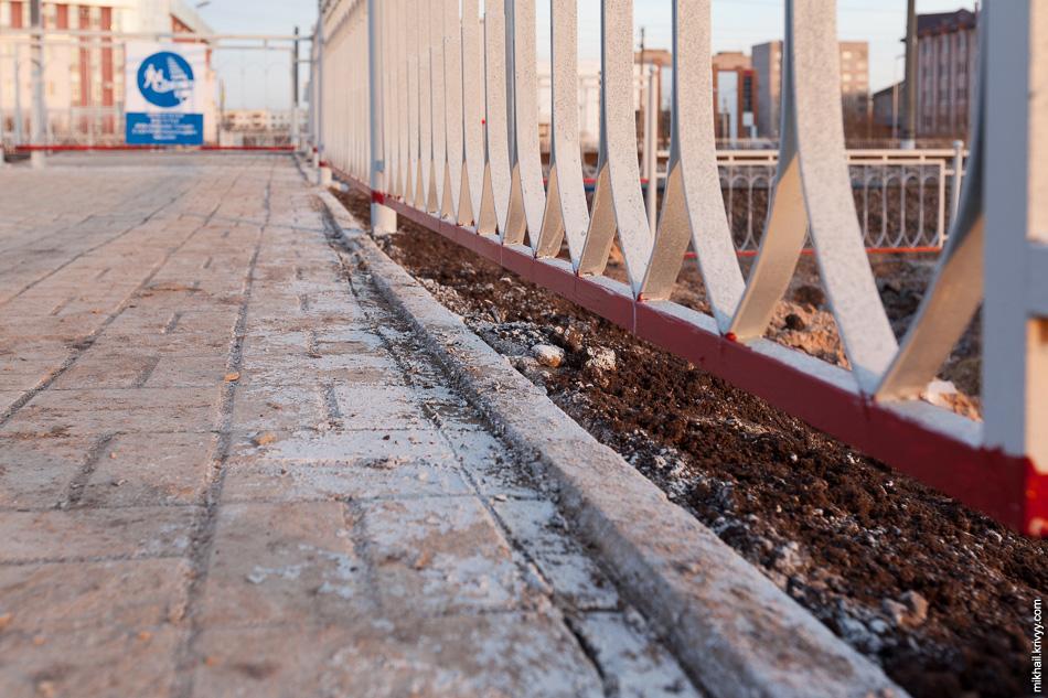 Сам переход сделан примерно с таким же отношением. Тротуарная плитка лежит криво, все вокруг покрыто краской, везде наляпано цемента.