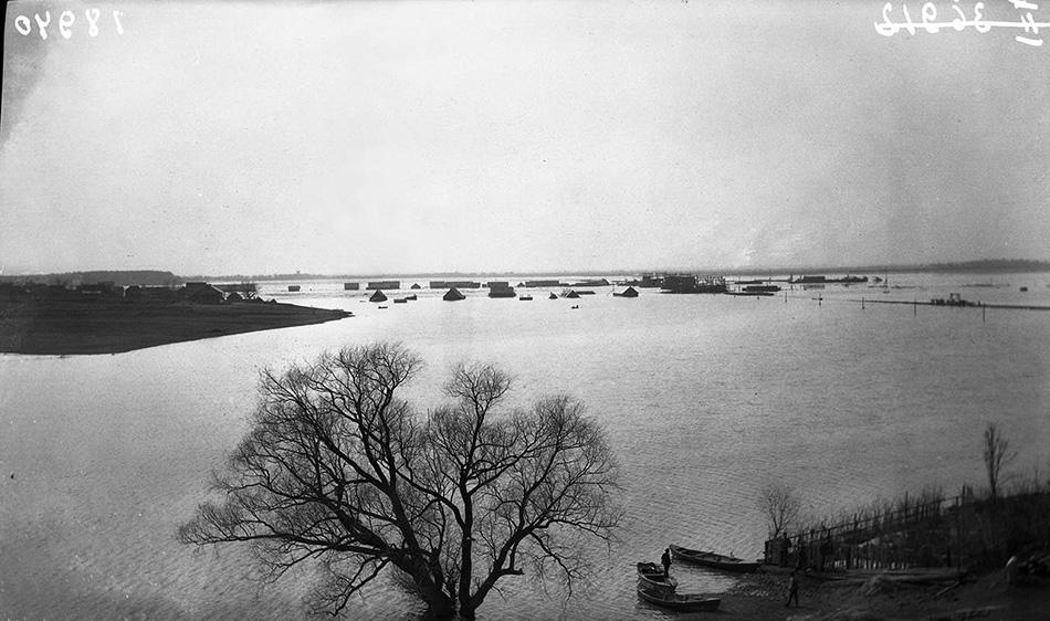 Паводок в апреле 1917 года. Видны жилые дома на берегах Волхова. Слева холм Рюрикова Городища, справа опоры строящегося моста.  Источник: www.oldrusphoto.ru.