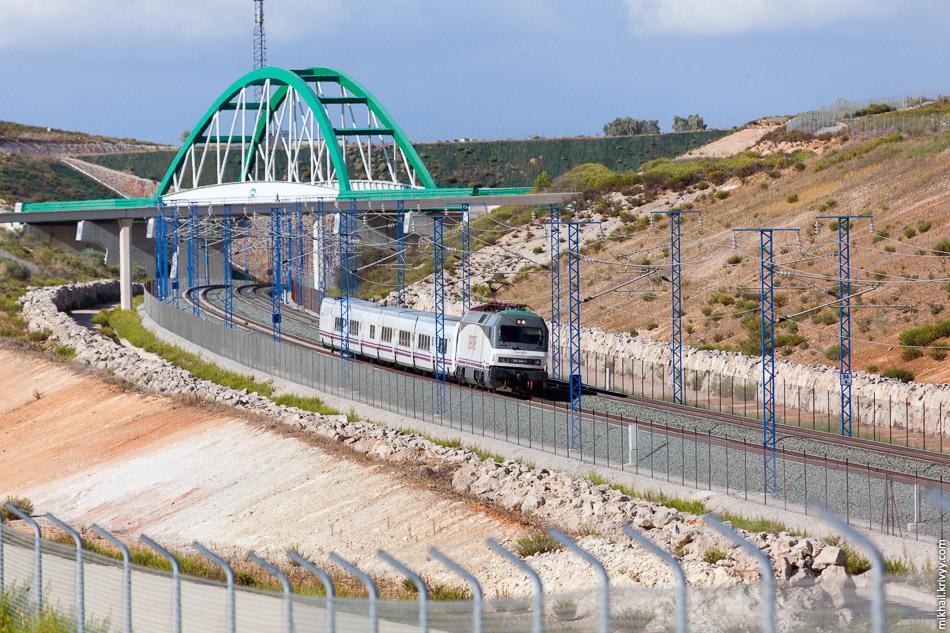 Поезд ALTARIA 09330 Мадрид - Альхесирас пропускает встречный состав перед станцией Антекера Санта-Анна. После станции он уйдет с высокоскоростной линии и пойдет по однопутному участку с иберийской колеей.