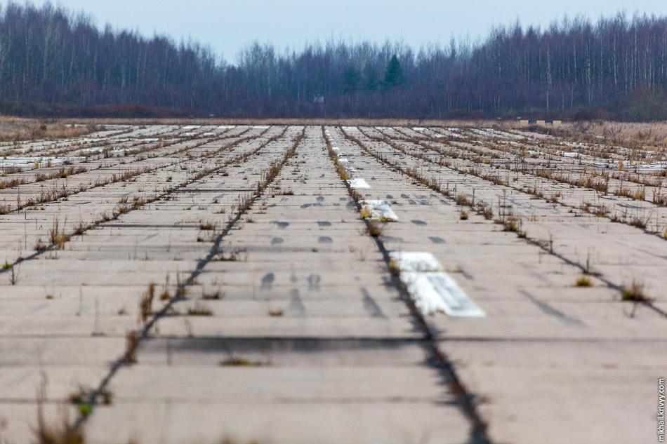ВПП аэропорта Кречевицы. У леса видны останки здания БПРМ (ближний приводной радиомаяк) и КРМ (курсовой радиомаяк).