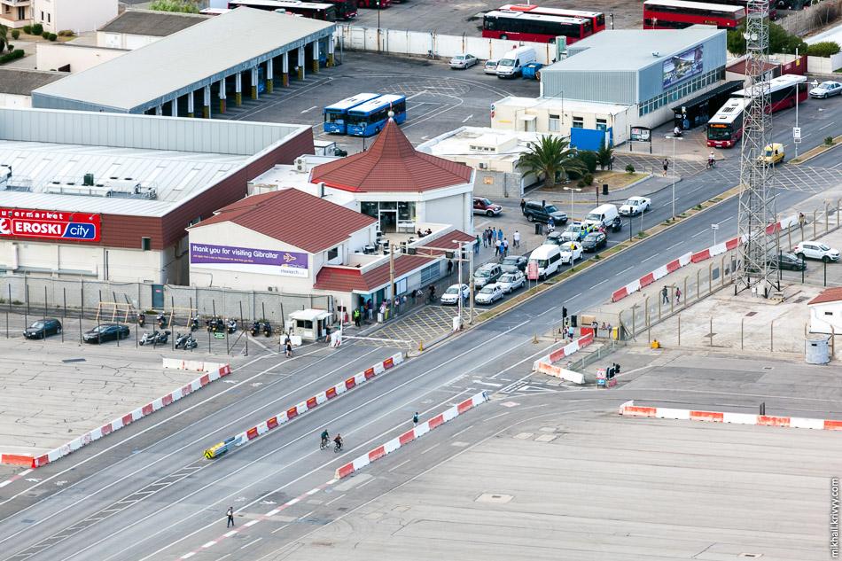 Переход через ВПП гибралтарского аэропорта закрыли. Готовится к вылету бизнес Jet. Синие автобусы на заднем плане - городской общественный транспорт Гибралтара.
