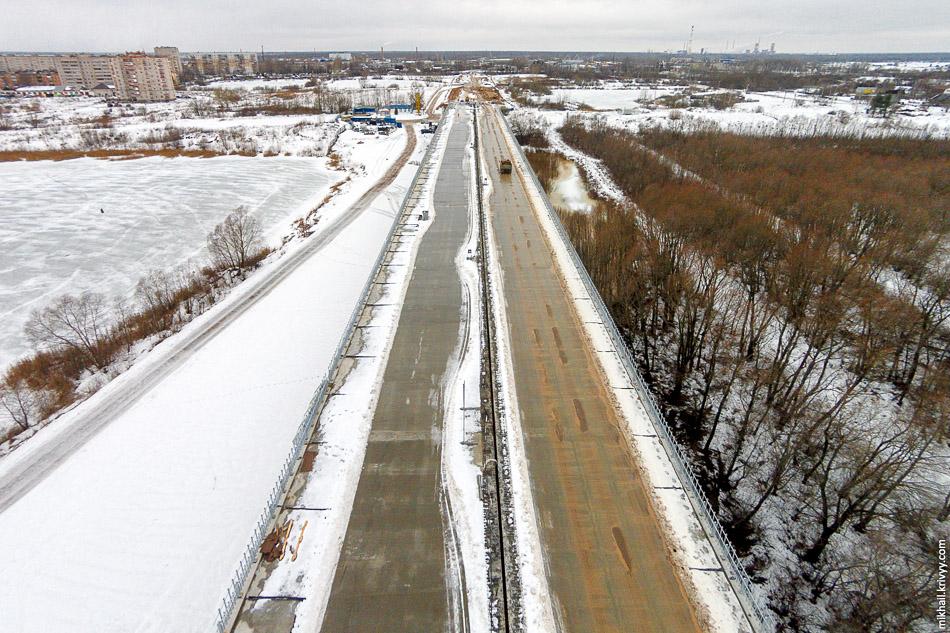 Строители уже пользуются мостом по прямому назначению - возят грунт и песок. Вид в сторону улицы Большой Санкт-Петербургской.