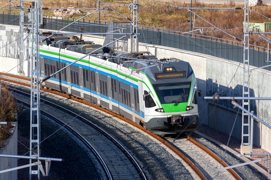 Электропоезд JKOY Class Sm5-11 следующий в сторону станции «Аэропорт» («Lentoasema»).
