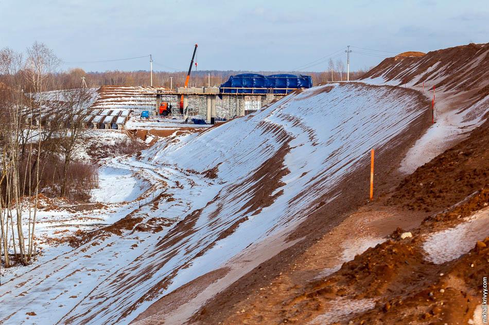 Автомагистраль М11 подходит к мосту через Волхов на небольшой насыпи. Из-за этого путепровод над автомагистралью также несколько выше чем обычно. Размеры насыпи сразу бросаются в глаза.