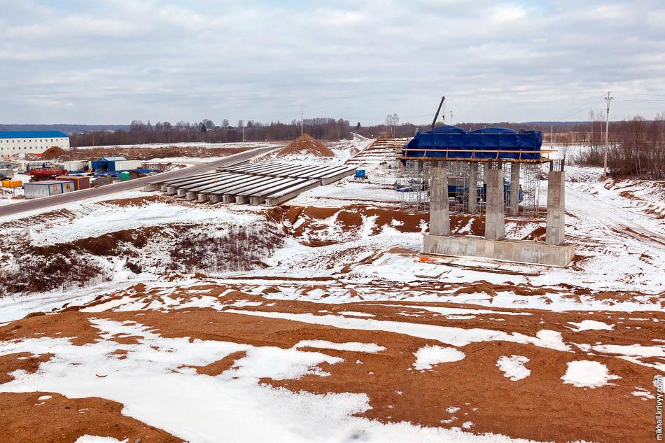 Вид с насыпи будущего путепровода. Пролетные строения временно складированы рядом со строящимися опорами.
