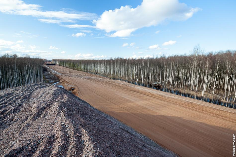 15. На км 542,3 устроен склад щебня. Гора высотой почти до макушек деревьев. Вид в сторону Санкт-Петербурга, виден путепровод на км 542,7.
