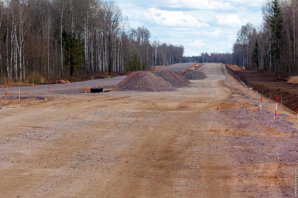 27. На правом берегу степень готовности намного выше. Дорога отсыпана песком и щебнем, примерно на 30-40% площади уже лежит черновой слой асфальта.