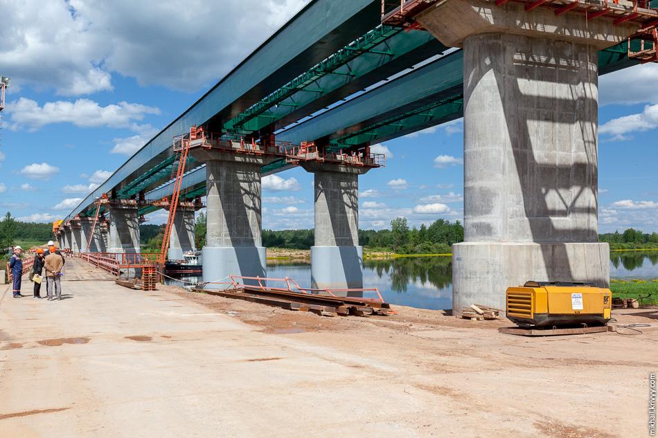 На центральной части моста пролетные строения устанавливают в проектное положение. После этого можно будет приступать к заливке плиты проезжей части.