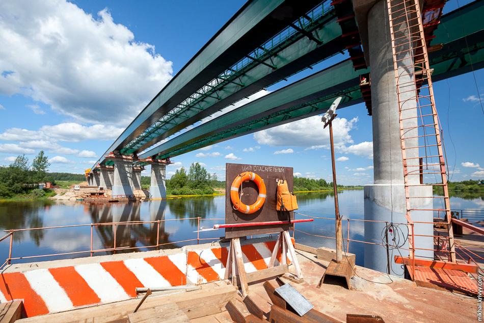 Справа опора №11. Она находится прямо по центру реки Волхов. Здесь при проведении работ вскрылись некоторые сложности, вызвавшие задержки строительных работ.