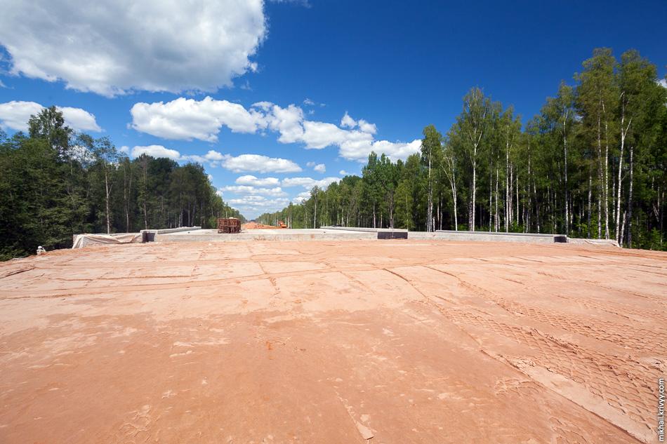 Вид с проезжей части. Путепровод ожидает бетонирования переходной плиты. Переходная плита предназначена для сглаживания передачи нагрузки с насыпи на опоры путепровода.