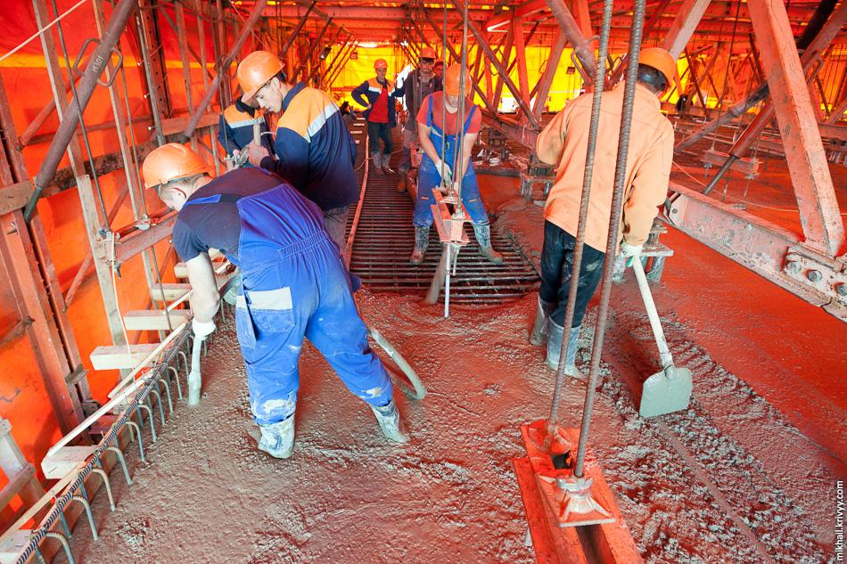 Внутри агрегата производится заливка плиты проезжей части. Когда бетон застывает, агрегат на специальных роликах передвигается дальше.