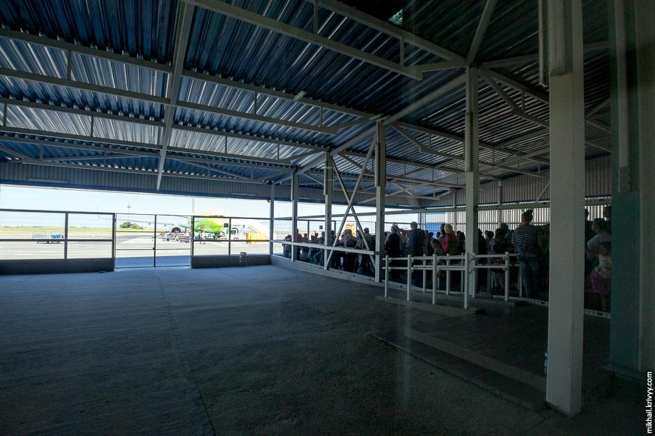 Перед выходом всех пассажиров загоняют в клетку на улице. Там негде сидеть, и пассажиры при +36 стоят и ждут, когда сотрудники аэропорта выловят всех заблудших и начнут всех загружать в самолет.