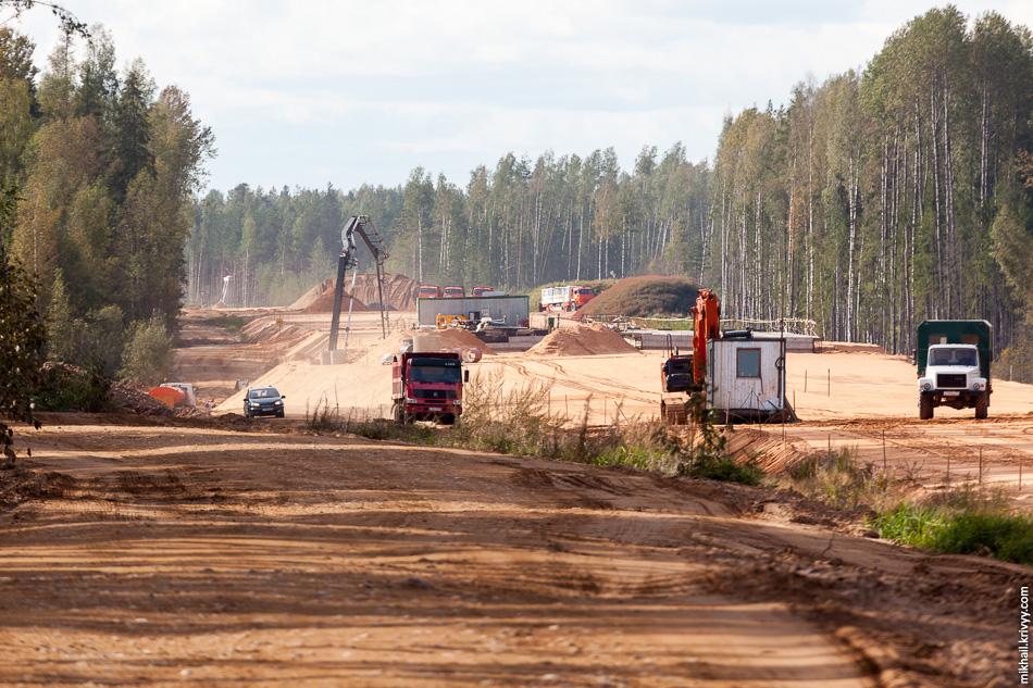 23. 511 км. Примерно с этого места начинается сухой сосновый лес и песчаные почвы. Песок для строительства автомагистрали добывается в карьерах, находящихся в непосредственной близости от места строительства. Это в том числе позволило так быстро отсыпать дорогу.
