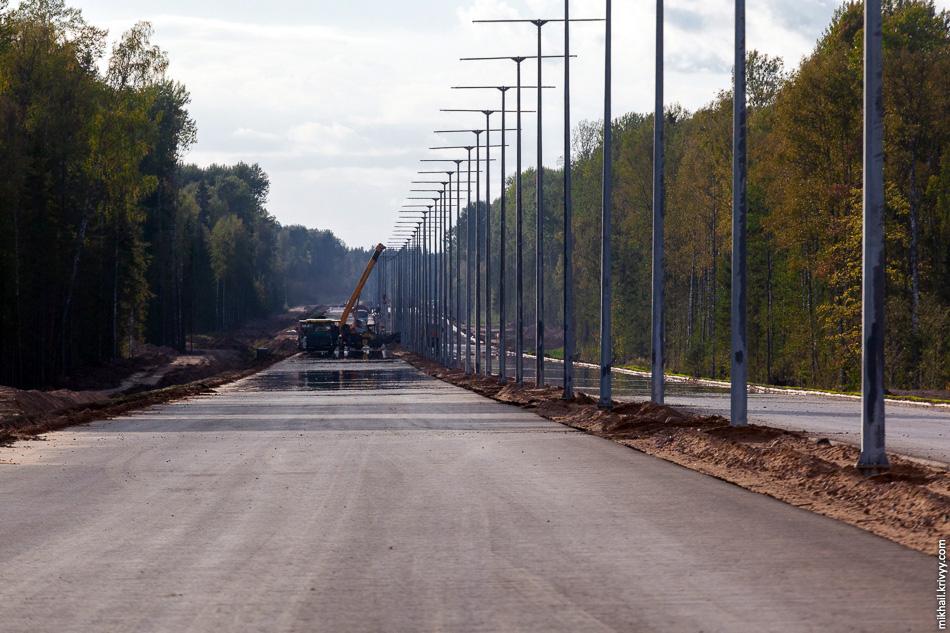 50. 483 км, вид в сторону Санкт-Петербурга. Только что уложен очередной слой асфальтового покрытия, ведётся демонтаж асфальтоукладчика. Перевозить по временным грунтовым дорогам агрегат, укладывающий асфальт сразу во всю ширину проезжей части, не так просто.