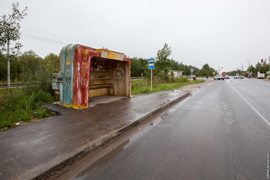 Маленькая автобусная остановка на выезде из города. Таких типовых остановок много, выполнены из композитного материала типа стекловолокна.