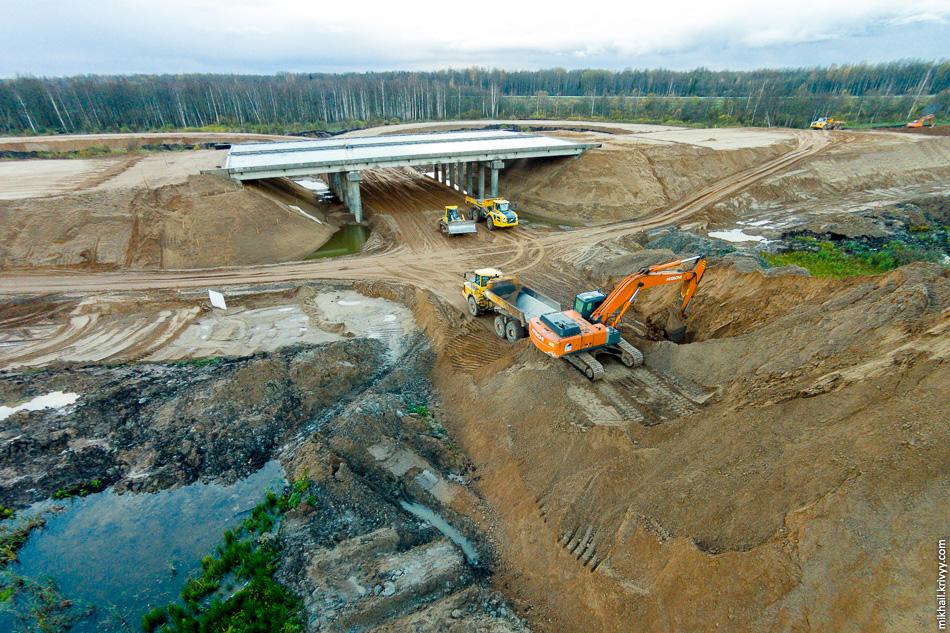 Буквально в трехстах метрах в сторону Москвы (ПК 5451+29) ведется строительство еще одного путепровода — на выходе с автомагистрали М11 к пункту взимания платежей. Путепровод практически готов, ведутся активные работы по насыпям. После того как насыпи будут готовы, строители приступят к обустройству переходных плит, гидроизоляции, ограждений и асфальтового покрытия.