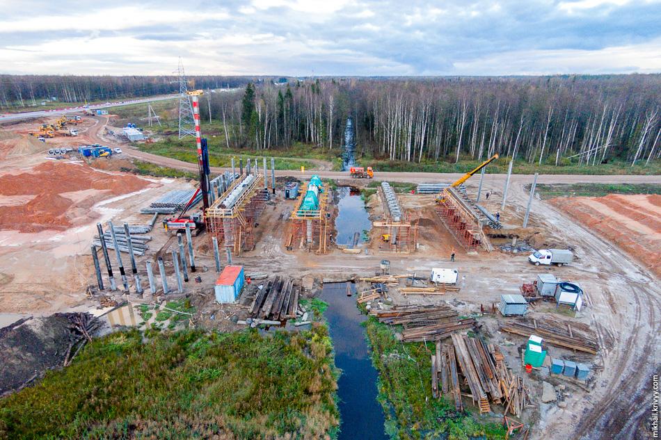 Сразу за путепроводом над М10 «Россия» ведется строительство моста через реку Питьба. В этом месте река больше похожа на небольшую канаву. Тем не менее, весной она заливает всю округу.
