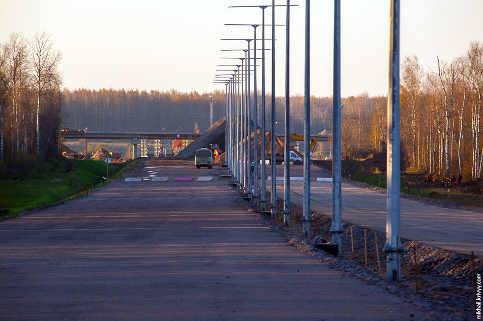 Вид назад, в сторону Санкт-Петербурга. Там виднеется путепровод на пересечении с автодорогой Савино — Селище. Лес на заднем фоне находится на другом берегу реки Волхов.