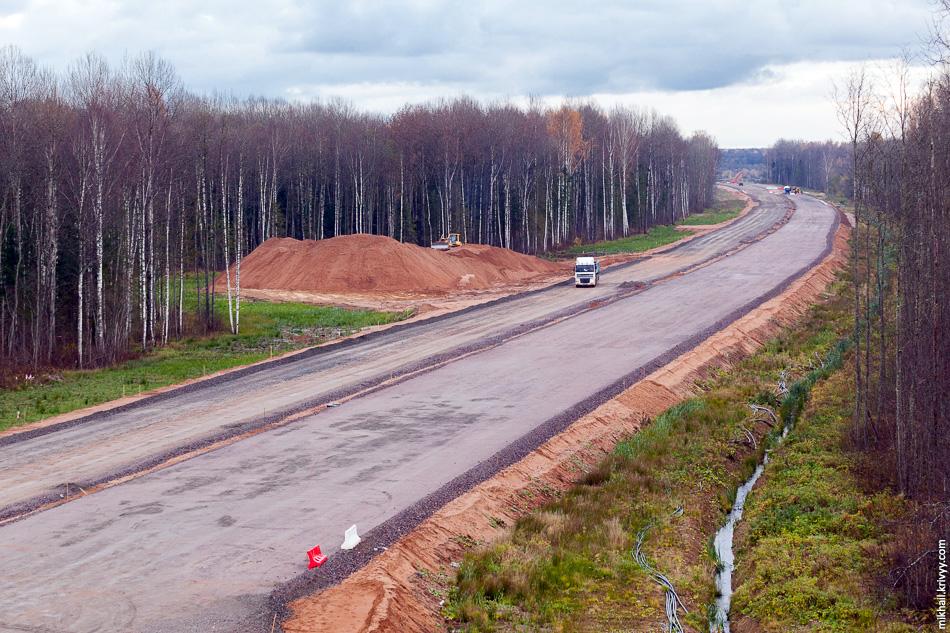 Вид в сторону Москвы. Проезжая часть справа подготовлена к укладке асфальта. Она идеально выровнена и проезд строительной техники по ней закрыт.